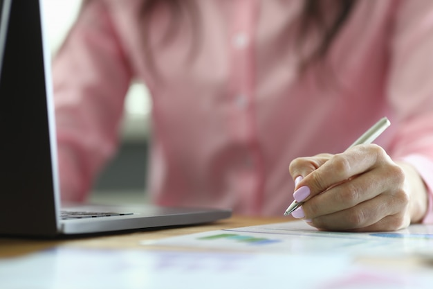 Biznesowa kobieta sprawdza dane w raporcie i na laptopie