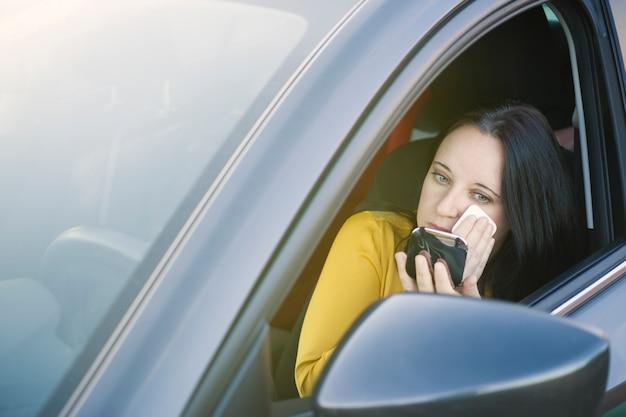 Biznesowa kobieta stawia na makeup w samochodzie z niebieskimi oczami podczas gdy w korku ulicznym