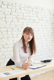 Biznesowa kobieta stoi przy stole z raportami biznesowymi i patrzy w kamerę.