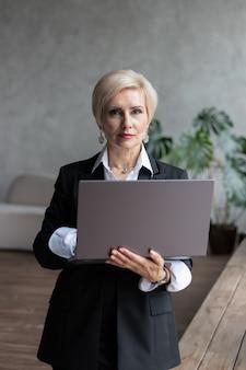 Biznesowa kobieta stoi z laptopem w biurze