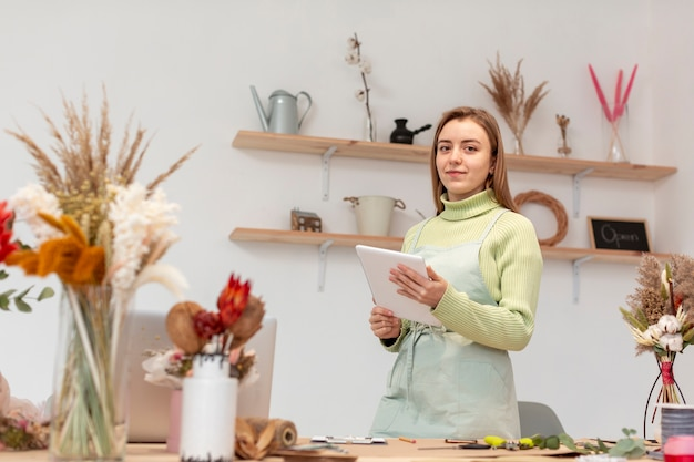 Biznesowa kobieta trzyma cyfrową pastylkę w jej swój sklepie