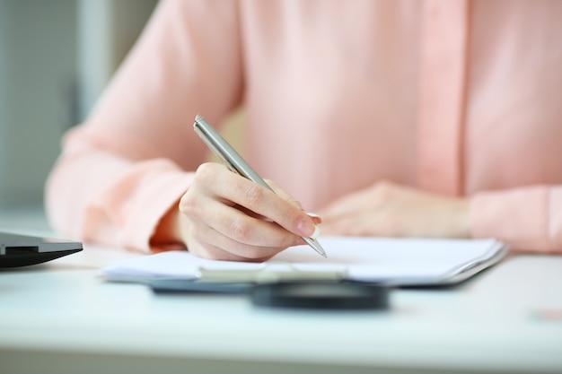 Biznesowa kobieta trzyma pióro w ręce i podpisuje kontrakt z głębią pola wizerunek