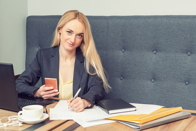 Biznesowa kobieta trzyma smartphone i pisze na pustym miejscu przy biurem