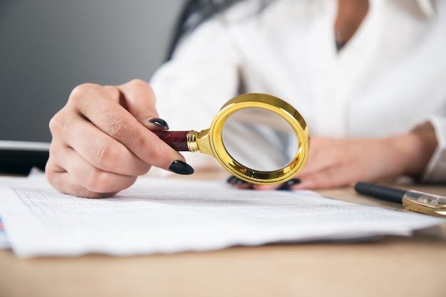 Biznesowa kobieta trzyma szkło powiększające i dokumenty