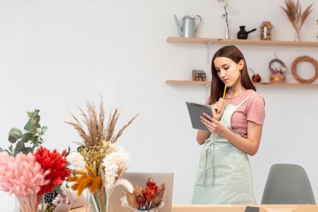 Biznesowa kobieta używa cyfrową pastylkę w jej swój sklepie