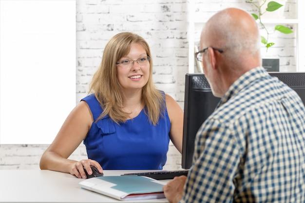 Biznesowa kobieta używa laptop i dawać radzi jej klient.