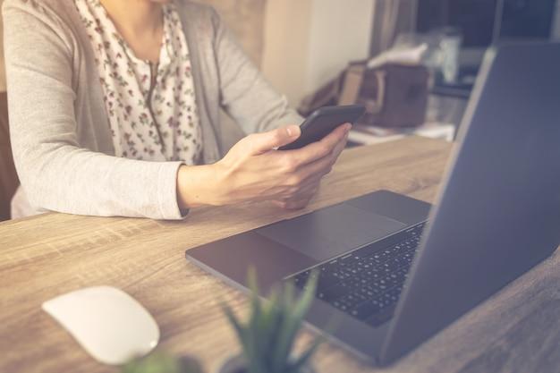 Biznesowa kobieta używa laptop robi online aktywności i trzyma telefon na drewno stole.