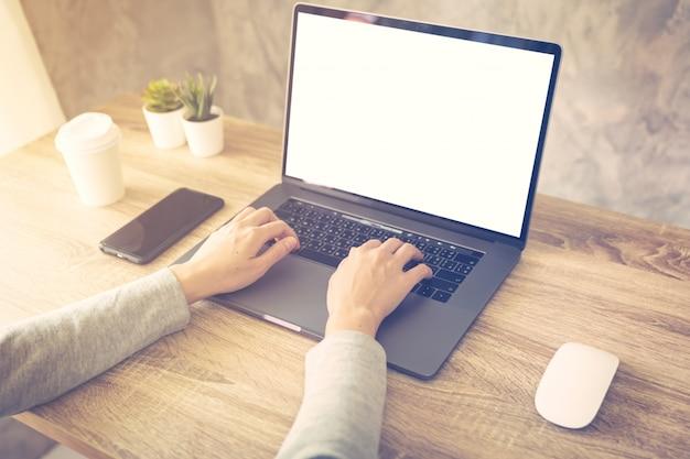 Biznesowa kobieta używa laptop robi online aktywności na drewno stołu biura w domu.