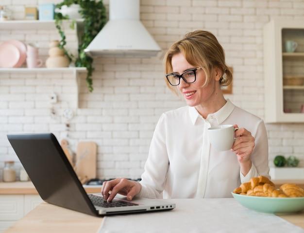 Biznesowa kobieta używa laptop w kuchni