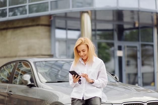 Biznesowa kobieta używa mądrze telefon na zewnątrz biurowego centrum