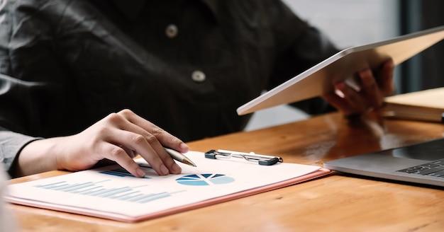 Biznesowa kobieta używa pastylka komputer dla analiza pieniężnego raportu
