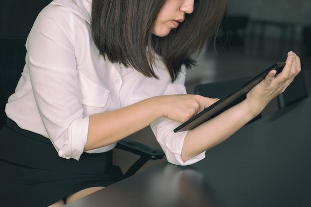 Biznesowa kobieta używa pastylkę na stole