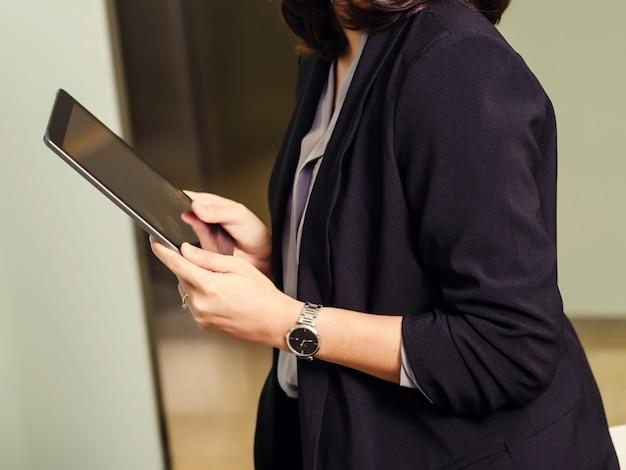 Biznesowa kobieta używa pastylkę w jej biurze