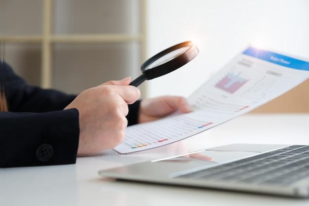 Biznesowa kobieta używa powiększać przeglądać bilans rocznego. audyt i sprawdzenie rzetelności przed inwestycją.