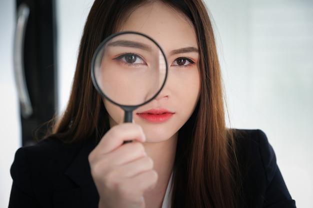 Biznesowa kobieta używa powiększać używać rewizi lub skanuje pojęcie.