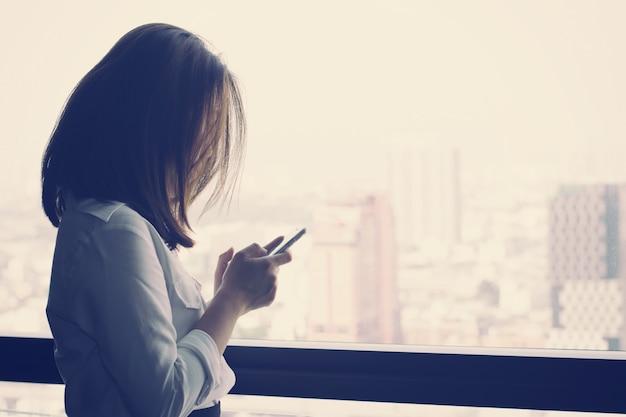 Biznesowa kobieta używa smartphone i patrzejący miasto widok