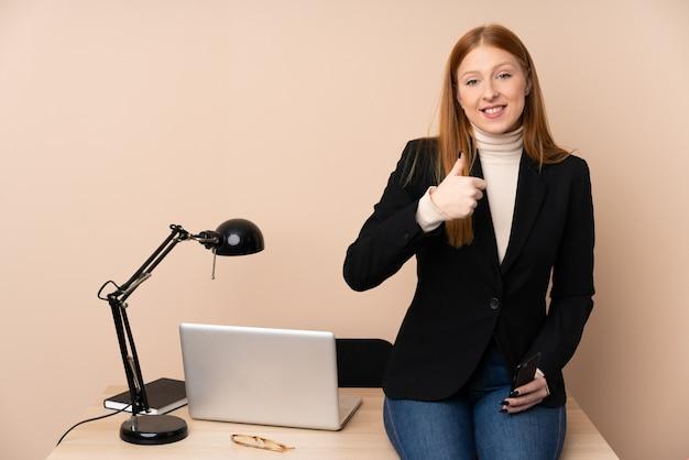 Biznesowa kobieta w biurze daje aprobata gestowi