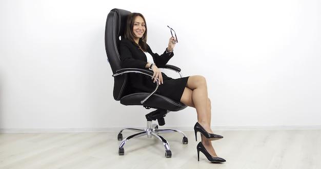 Biznesowa kobieta w biurze dziewczyna w garniturze z okularami w dłoni siedzi na krześle