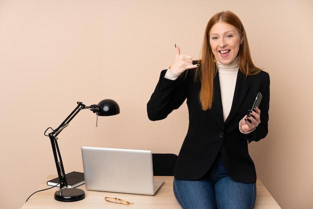 Biznesowa kobieta w biurze robi telefonu gestowi