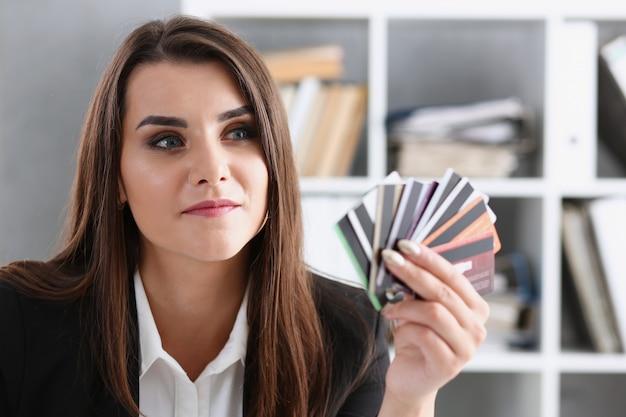 Biznesowa kobieta w biurze trzyma w ręce plastikową kredytową kartę debetową
