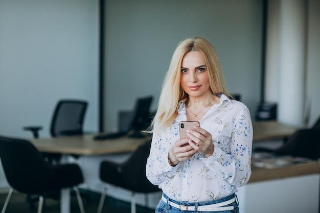 Biznesowa kobieta w biurze używać telefon