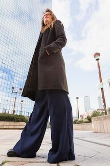 Biznesowa kobieta w czarnej eleganckiej kurtki trwanie outside