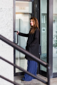 Biznesowa kobieta w czarnej kurtce wchodzić do budynek