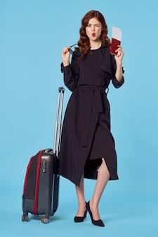 Biznesowa kobieta w czarnym płaszczu paszportu wakacyjnego i biletów lotniczych