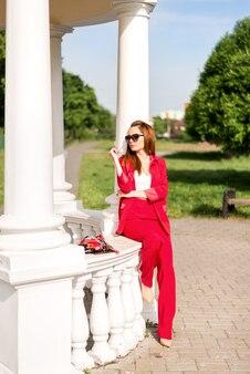 Biznesowa kobieta w czerwonym kostiumu blisko białej altany