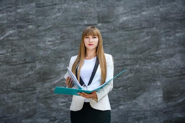 Biznesowa kobieta w garniturze pozuje z folderem na abstrakcyjnym tle