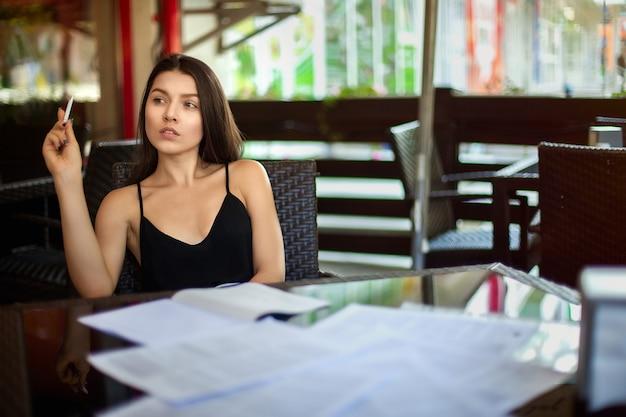 Biznesowa kobieta w kawiarni wypełnia dokumenty. refleksje pracuj poza biurem