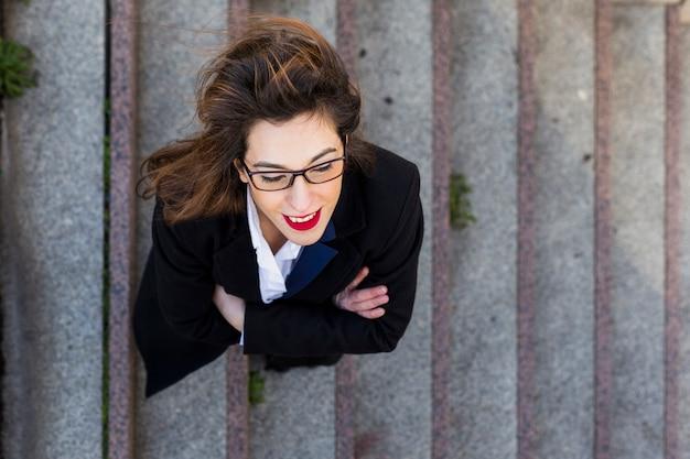 Biznesowa kobieta w kostium pozyci na schodkach outside