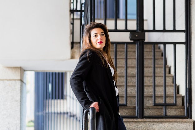 Biznesowa kobieta w kostiumu opiera na poręczu