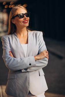 Biznesowa kobieta w niebieskiej kurtce przy centrum biurowym