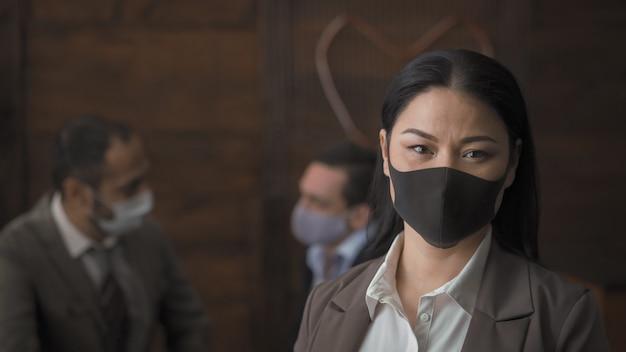Biznesowa kobieta w ochronnej maski stoi w biurze