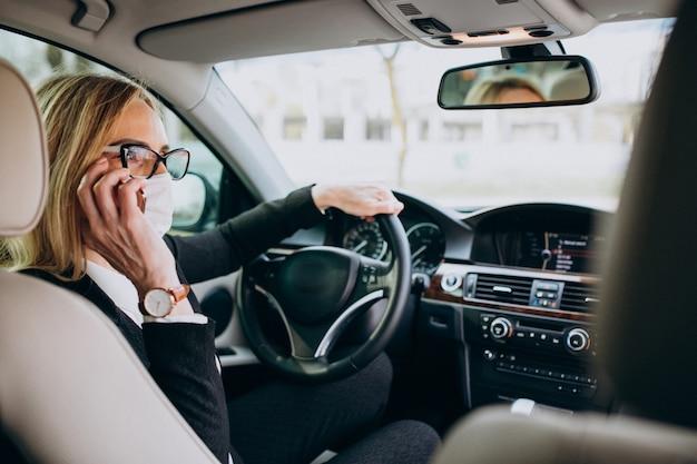 Biznesowa kobieta w ochrony maski obsiadaniu wśrodku samochodu