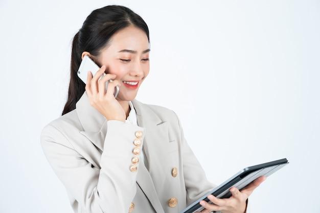 Biznesowa kobieta w popielatym kostiumu używać telefon i pastylkę łączyć z klientami.