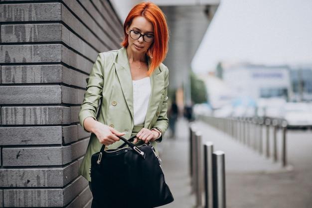Biznesowa kobieta w zielonej kostium pozyci ścianą