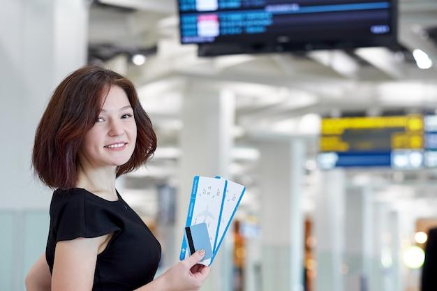 Biznesowa kobieta z biletami i kredytową kartą czeka odjazd blisko tablicy informacyjnej na lotnisku