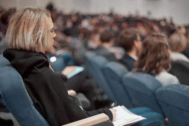 Biznesowa kobieta z dokumentami biznesowymi siedząca w sali konferencyjnej