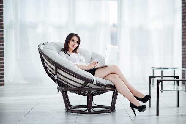Biznesowa kobieta z dokumentami siedząca wokół wygodnego krzesła