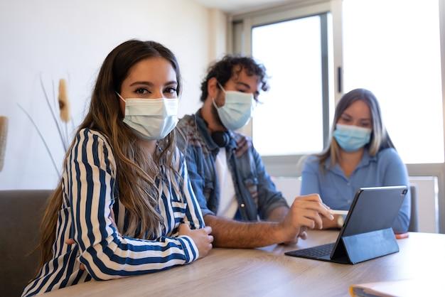 Biznesowa kobieta z maską patrząca na kamerę podczas kreatywnego spotkania