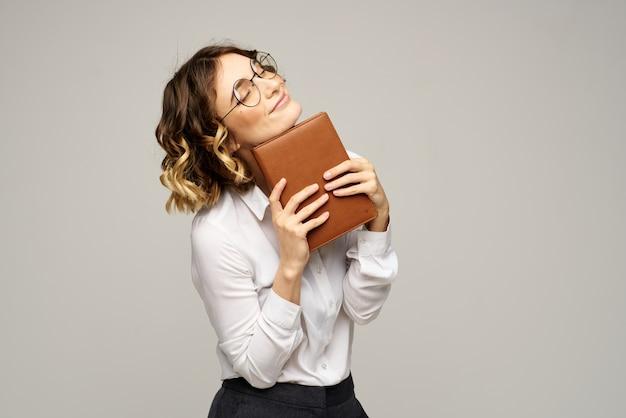 Biznesowa kobieta z notatnikiem i okularami na jasnym tle