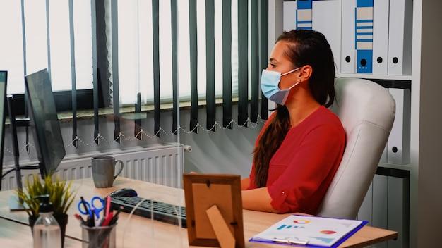 Biznesowa kobieta z ochroną maski analizuje roczne wykresy siedząc w biurze z poszanowaniem dystansu społecznego. freelancer pracujący w nowym, normalnym biurze, rozmawiający na czacie podczas wirtualnej konferencji online