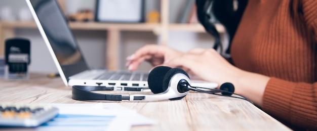 Biznesowa kobieta z słuchawką i komputerem na stole