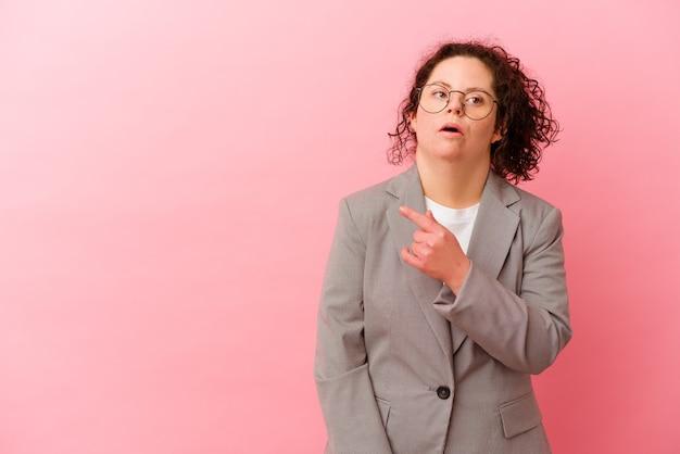 Biznesowa kobieta z zespołem downa odizolowana na różowym tle skierowana w bok