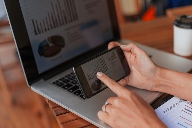 Biznesowa kobieta za pomocą smartfona do analizowania danych finansowych. ludzie i technologia.