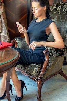 Biznesowa kobieta za pomocą telefonu komórkowego.