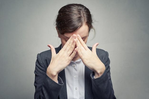 Biznesowa kobieta zakrywająca twarz z jej ręką