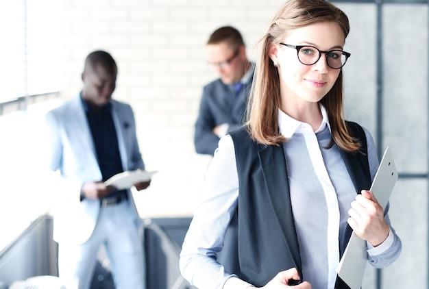 Biznesowa kobieta ze swoim personelem, ludzie grupują się w tle w nowoczesnym, jasnym biurze w pomieszczeniu